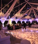 Patterned dance floor with white drapery and chandeliers