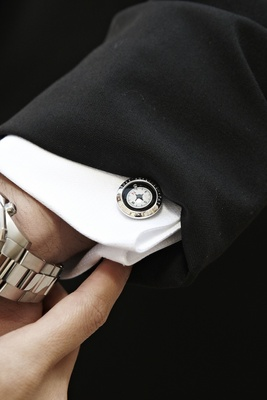 Silver compass cufflink on groom's tuxedo shirt cuff