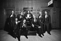 Black and white photo of groomsmen by shoe shining