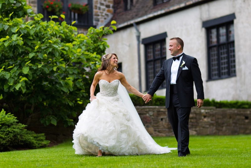 Bride in a strapless Lazaro dress with beaded bodice, ruffled skirt walks with groom in black tuxedo