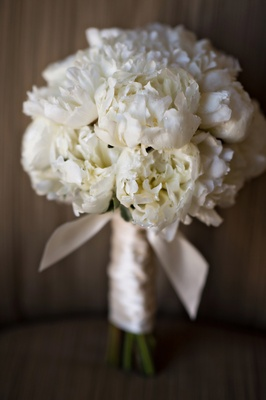 white peony bridal bouquet with dew droplets, tied with blush ribbon