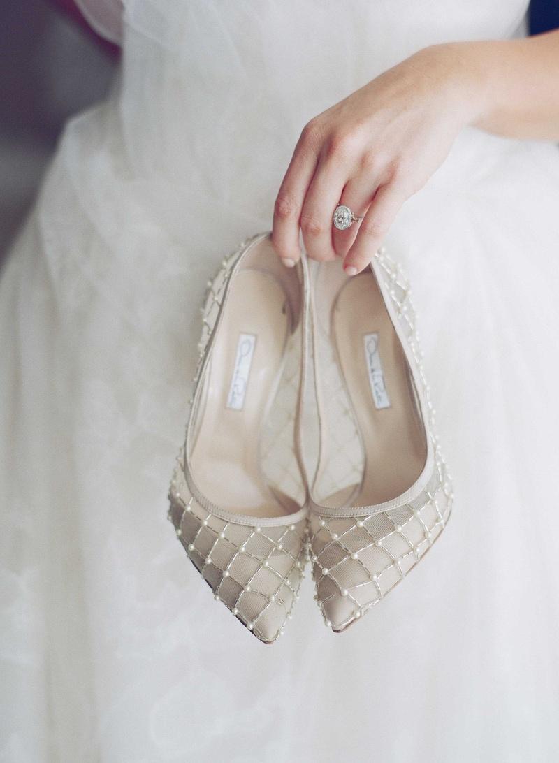 Bride with oval cut diamond engagement ring holding Oscar de la Renta wedding pumps