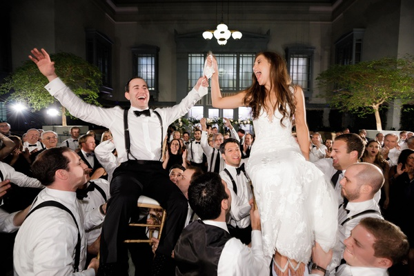 bride and groom on top of chairs during hora dance at jewish wedding reception chicago black white