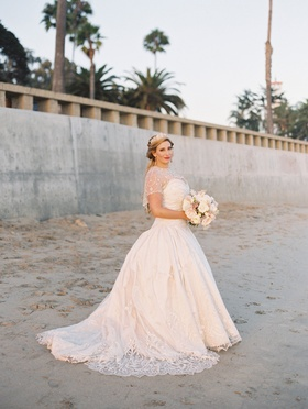 Bride in wedding dress Eve of Milady lace short sleeves sheer details bouquet on beach