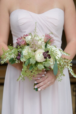 bridesmaid with draped dress bouquet of protea ranunculus and greenery fall bouquet ideas