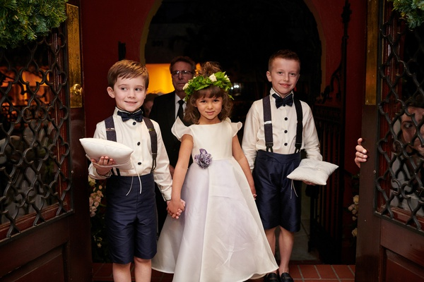 two ring bearers in shorts and suspenders hold hands with flower girl in floral crown