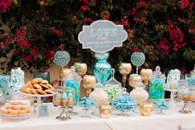 wedding dessert bar with gold, blue, and green featuring cake pops, cookies, blondies, and candy
