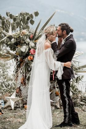 bride in daughters of simone wedding dress kiss groom man bun at boho ceremony lake como