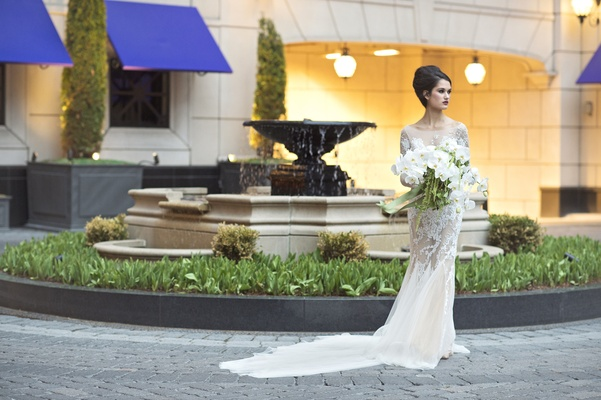 wedding styled shoot, model in lace ines di santo gown, large bouquet white orchids and amaranths