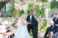 Bride and groom under ceremony structure with branches and flowers with friend as officiant