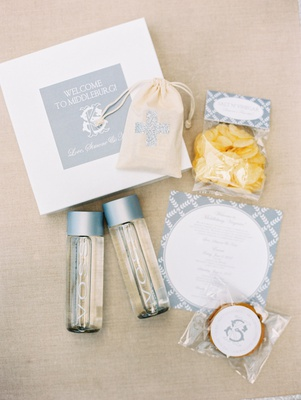welcome box with first aid kid, potato chips, cookie, and voss water bottles destination wedding