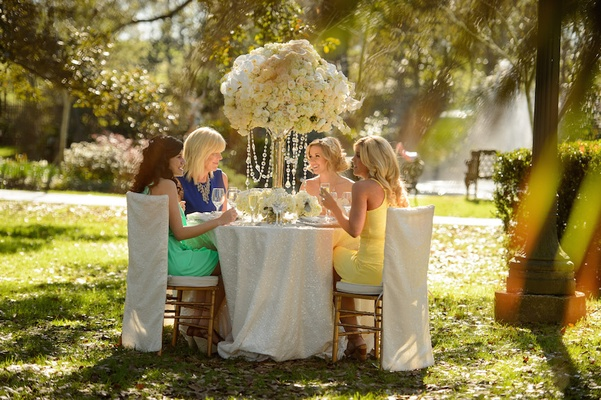 Bride and mother of bride with bridesmaids at outdoor table