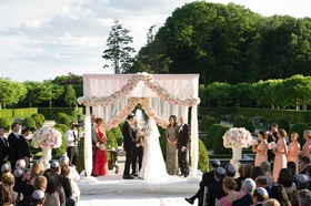 White chuppah with garland of pink and white flowers