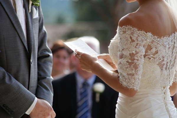 Woman holding handwritten paper note in wedding dress