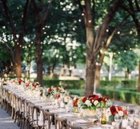 A rustic tablescape accented by red blooms stretches endlessly across an outdoor reception area.