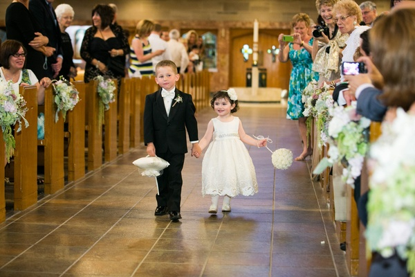 Flower girl and ring bearer hold hands down church aisle
