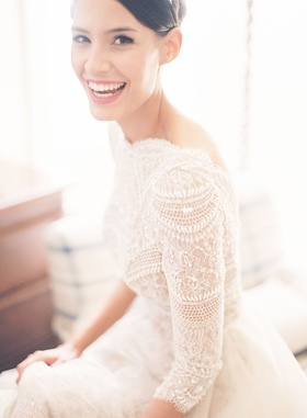 Bride in high bun smiling model in lace wedding dress three quarter sleeves and full skirt elegant