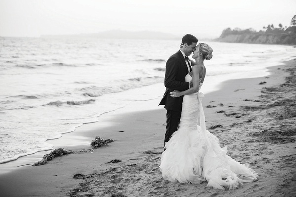 black & white photo of bride in vera wang gemma gown with groom in tux on beach