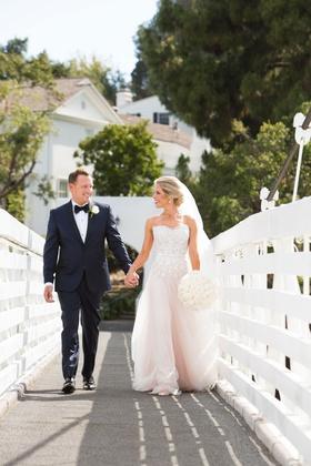 Bride in strapless wedding dress holding groom hand on bridge in california holding round bouquet