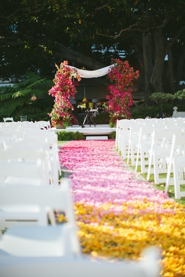 ombré aisle with pink and yellow flower petals and bougainvillea chuppah white chairs