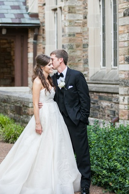 a groom kissing his beautiful bride on the cheek during their first look before the church ceremony