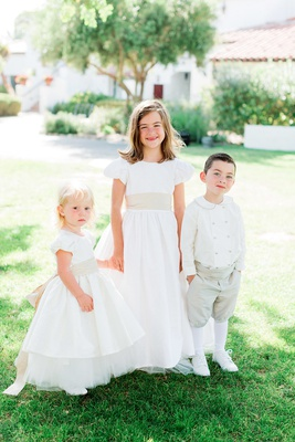 older flower girl holding hands of younger flower girl and ring bearer in old-fashioned attire