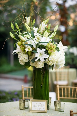 White linen with gold details and tall flower arrangement of white lily, hydrangea, and green orchid