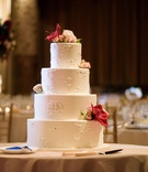 Classic round tier wedding cake with piping fresh flowers on each layer and monogram on second layer