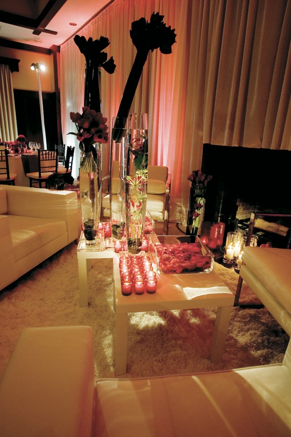 Conversation area with white couches and large red flower arrangements