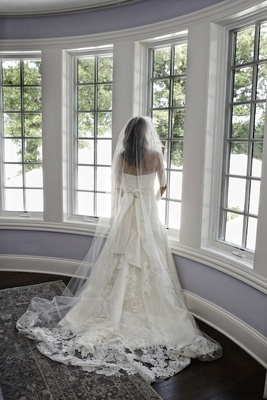 Bride with lace gown standing at bay window