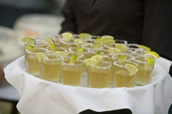 Tray-passed tequila cocktails with lime garnish
