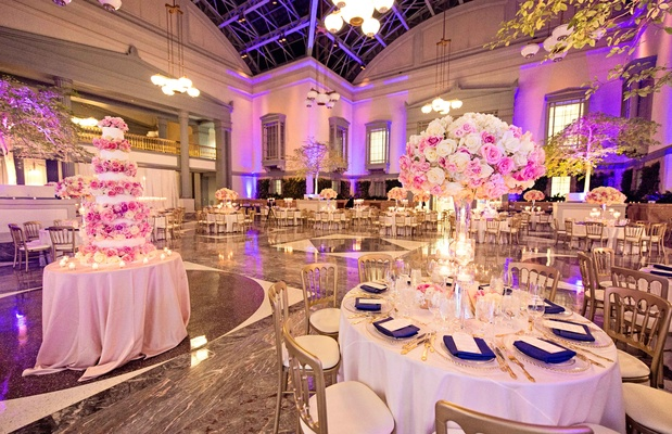 Library wedding venue with violet uplighting, white tablecloths, gold chairs, tall centerpieces