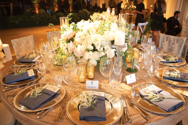 wooden table with white roses in centerpiece, gold votives, navy napkins with amaranthus