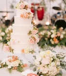wedding cake with fresh flowers pink peach white roses ranunculus flowers texture pattern linen