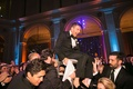 Guests hoisting up groom on chair during hora at brooklyn museum wedding purple lighting