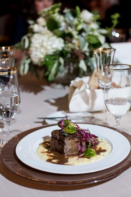 Wedding food long braised short rib of beef on charger plate low centerpiece gold rim glassware