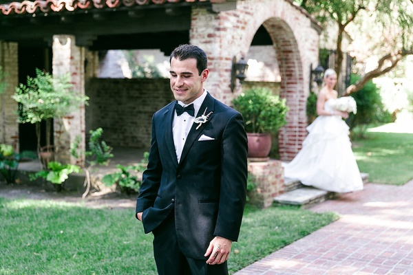Groom in black tuxedo waits to see bride in a strapless Hayley Paige dress with tiered skirt