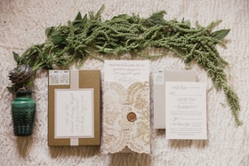invitations in neutral colors, pictured with greenery and succulents