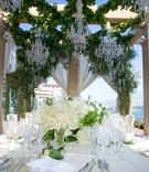 gold-rim charger plate white flowers with greenery on table crystal glassware ivory drapery greenery