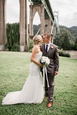 bride groom share kiss cathedral park portland oregon bridge outdoor wedding rustic chic gray tuxedo