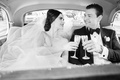 black and white photo of bride and groom in back of classic car with champagne flutes