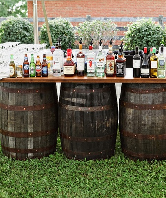 Farm wedding reception with a rustic bar set on old barrels