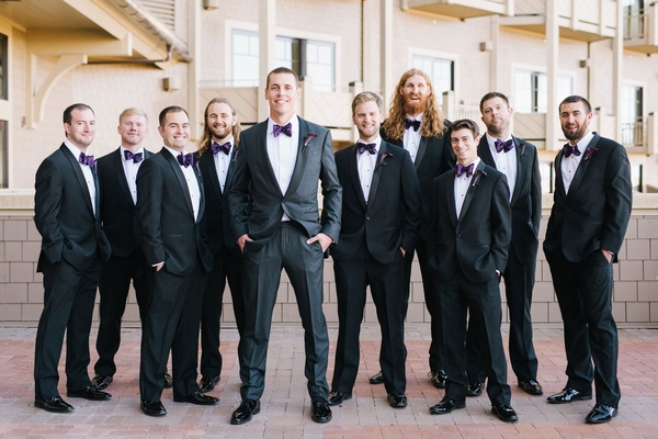 Wedding party groom and groomsmen in dark suits and purple bow ties matching fall wedding ideas