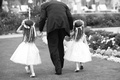 Black and white photo of flower girls walking with man in suit