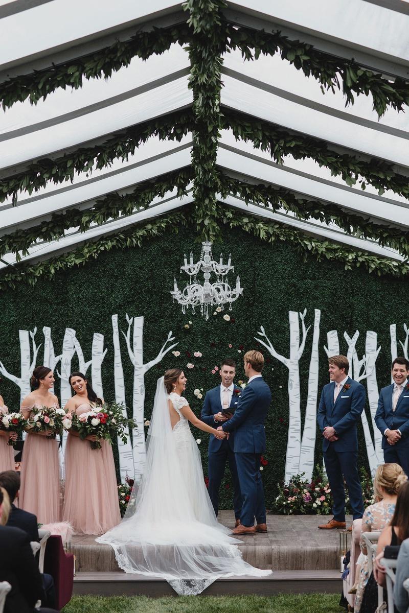 wedding ceremony decor clear top tent greenery chandelier hedge wall birch tree design bridesmaids