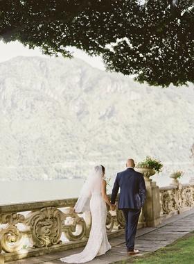 lake como wedding portrait bride and groom walking along railing by lake under tree