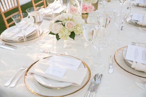 Place setting with gold-rimmed charger and tan napkin