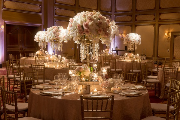 Wedding reception tables with rose and orchid centerpieces dripping with jewels