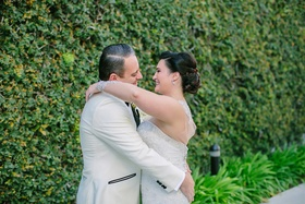 bride in martina liana hug white tuxedo jacket after first look