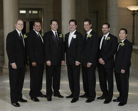 groom and groomsmen wearing black suits and orchid boutonnieres